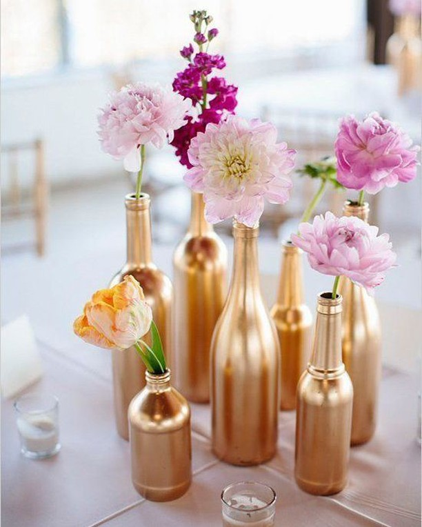 DIY Backyard Wedding Decorations On a Budget Table Centerpice of Glass bottles painted in gold color along with flowers in pink, purple and blush peach