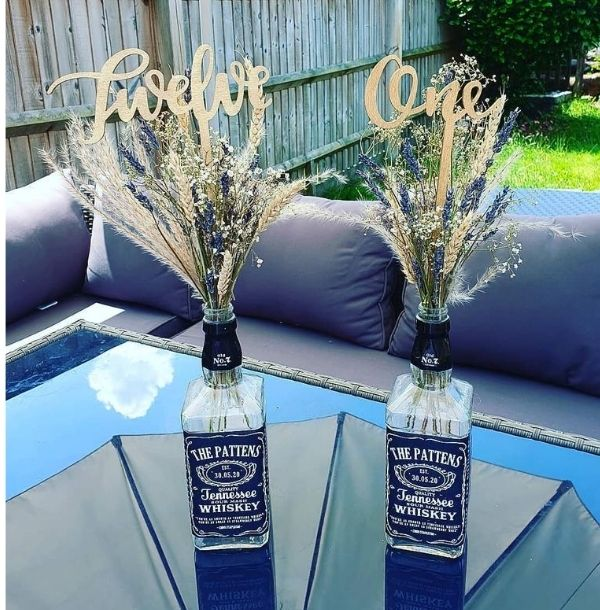DIY Backyard Wedding Decorations On a Budget Centerpiece made of whiskey bottles, rustic flowers bouquet and wooden table numbers Sprayed with gold paint