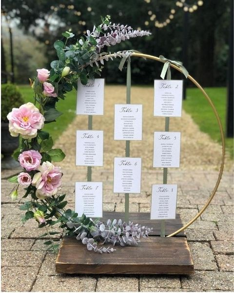 DIY Backyard Wedding Decorations On a Budget Hoops Seating Chart decorated with greenery and pink floral garland