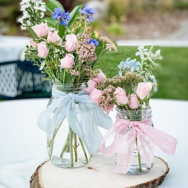 DIY Backyard Wedding Decorations On a Budget Two Sizes of mason jars with Pink and blue ribbon on top of a Wood Slice Centerpieces