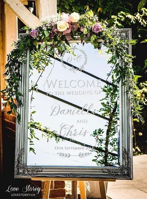 DIY Backyard Wedding Decorations On a Budget Mirror Welcome Sign with greenery and floral garland