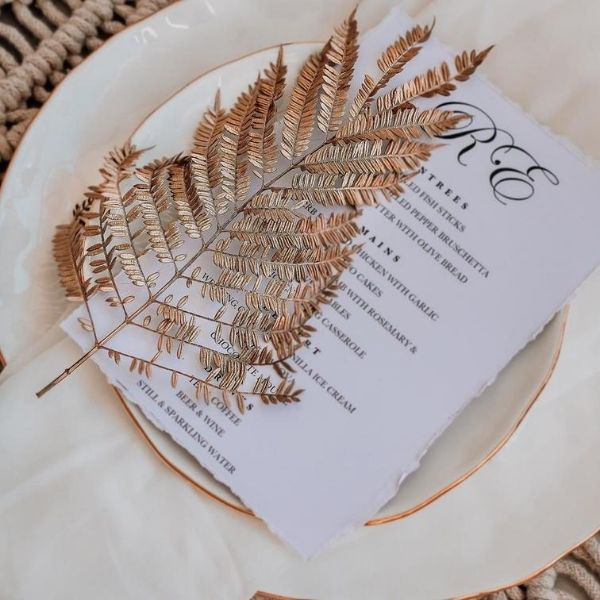 DIY Backyard Wedding Decorations On a Budget Table Setting Decoration metallic gold spray paint over plat size leaves